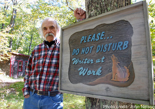 Blei on his own turf in Ellison Bay, Door County, standing in front of a sign welcoming—or, considering the coyote, possibly warning away—visitors to his converted chicken coop writer's studio. -- Photo by John Nelson